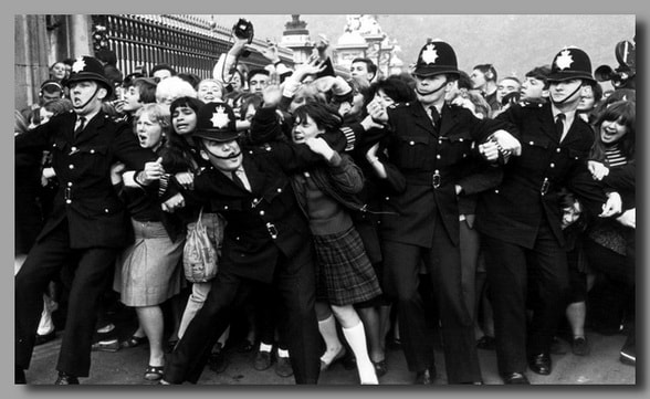Police keeping back a crowd of young fans outside Buckingham Palace, London, as pop group the Beatles receive their MBEs. (Photo by Central Press/Getty Images)